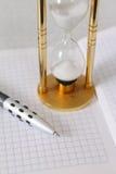Arena-vidrio con el lápiz y un cuaderno Fotos de archivo libres de regalías