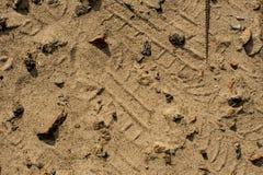 Arena y piedras fondo y textura Rastro del neumático en la arena Foto de archivo