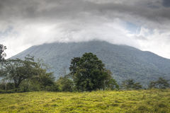 Arenal volcano in Costa Rica half covered with clouds Stock Images