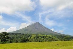 Arenal Volcano, Costa Rica. Arenal Volcano on a sunny day in Costa Rica with forest and field in foreground Stock Photo