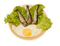 Arenques ahumados con el huevo frito y la ensalada aislados imagen de archivo