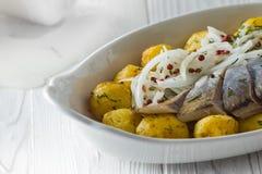 Arenques con las patatas y la cebolla fritas en una placa imagenes de archivo
