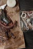 arenques e miúdos de ave frescos crus no saco de papel, preparação para salgar peixes Imagens de Stock
