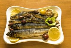 Arenques pequenos fritados e fumado Hering Báltico com limão e verdes na placa branca Foto de Stock