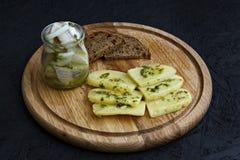Arenques salados en un tarro con las patatas hervidas y la salsa verde imágenes de archivo libres de regalías