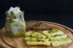 Arenques salados en un tarro con las patatas hervidas y la salsa verde fotografía de archivo
