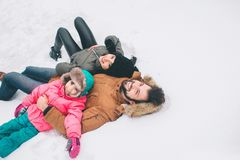 Arenthood, fashion, season and people concept - happy family with child in winter clothes outdoors Royalty Free Stock Image