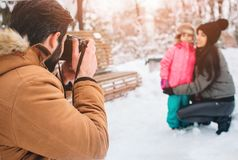 Arenthood, fashion, season and people concept - happy family with child in winter clothes outdoors. Take photos with Royalty Free Stock Images