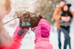 Arenthood, fashion, season and people concept - happy family with child in winter clothes outdoors. Take photos with Stock Images
