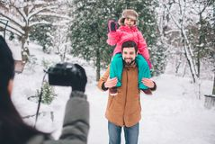 Arenthood, fashion, season and people concept - happy family with child in winter clothes outdoors. Take photos with Stock Photos