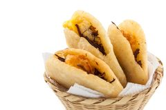 Arepa de huevo. Traditional Colombian fried arepa filled with egg and shredded meat on white background