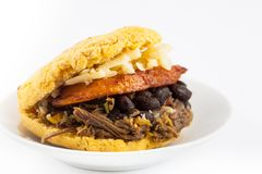 Arepa filled with shredded beef, black beans, plantain and cheese