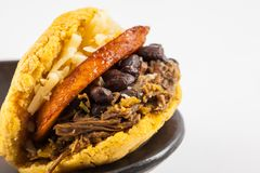 Arepa filled with shredded beef, black beans, plantain and cheese served in a black ceramic dish