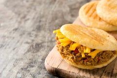 Arepa met verscheurd rundvlees en kaas op houten achtergrond Venezolaans typisch voedsel royalty-vrije stock afbeelding