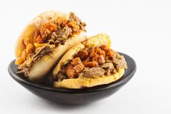 Arepas filled with shredded beef and pork rind served in a black ceramic dish