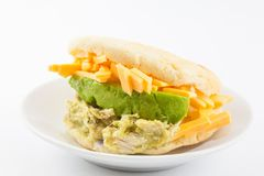 Arepas filled with shredded chicken and avocado served in a black ceramic dish