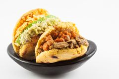 Arepas with two different fillings served in a black ceramic dish. On white background stock images