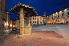 Arezzo, Italy. Piazza Grande and old well. Arezzo, Italy. Old well located on Piazza Grande square at dusk stock photo