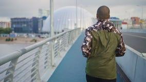 Arfican Amerikaanse jonge mens die aan muziek opleiding op stedelijke brug luisteren stock footage