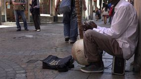 Arfican immigrant playing music on the street stock video footage