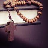 Arg halsband för kristen på boken för helig bibel arkivfoto