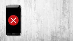 Arg symbol på den svarta smartphonen på vit träbakgrund royaltyfri bild