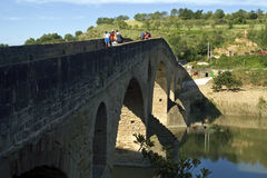 中世纪桥梁、香客和河Arga,西班牙 免版税图库摄影