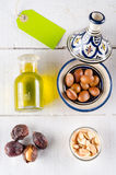 Argan nuts and oil on white wooden tabletop with green label Stock Photography