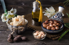 Argan oil and fruits with Shea butter and nuts. Still life of Argan oil and fruit and shea butter with nuts on a wooden table with flowers Royalty Free Stock Photos