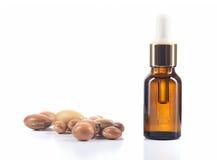 Argan olie en argan noten op witte achtergrond. Stock Fotografie