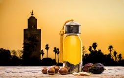 Argan olie en vruchten met landschap bij zonsondergang stock foto