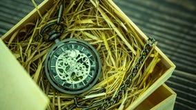 Argano dell'orologio da tasca di lasso di tempo su paglia di frumento naturale in una scatola di legno video d archivio