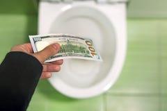 Argent affleurant en bas de la toilette, billets d'un dollar de jets dans la toilette, concept de perte, fin, foyer sélectif image libre de droits