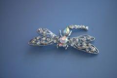 argent, or blanc, broche de libellule de platine sur un tissu bleu de cuir de suède Images stock