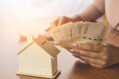 Argent calculateur de main de femme avec le modèle de maison sur la table en bois surfaçant pour acheter ou louer à la maison Photo stock