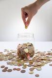 Argent d'économie dans un pot en verre Photo stock