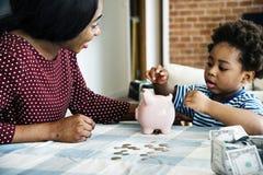 Argent d'économie de maman et de fils vers la tirelire images stock