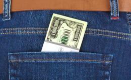 Argent dans la poche de jeans Photographie stock libre de droits