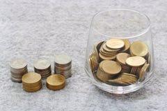Argent dans le verre avec l'élevage de pile de pièce de monnaie Images stock