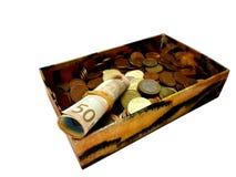 Argent dans une vieille boîte, des billets de banque et des pièces de monnaie, d'isolement Photographie stock