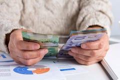 Argent de Canada Dollars Femme retir?e tenant la facture sur le bureau de bureau photo libre de droits