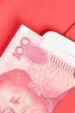 Argent de Chinois ou de 100 billets de banque de yuans dans l'enveloppe rouge, en tant que Chinois Photo libre de droits