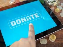 Argent de donation en ligne par le comprimé photo stock
