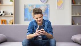 Argent de perte d'adolescent masculin soucieux dans le casino en ligne, manque de contrôle parental banque de vidéos