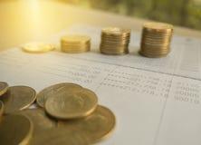 Argent de pièce de monnaie de pile avec des finances et des opérations bancaires de livre de comptes Photographie stock