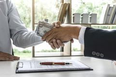 Argent de poignée de main d'homme d'affaires des billets d'un dollar dans des mains de tandis que photographie stock libre de droits