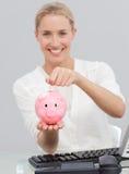 Argent de sourire d'économie de femme d'affaires dans un piggibank photographie stock
