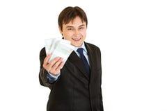 Argent de sourire de fixation d'homme d'affaires dans sa main Images libres de droits