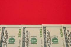 Argent, dollars d'une manière ordonnée présentés sur un fond rouge avec une copie de l'espace Photographie stock libre de droits