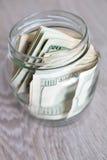 Argent Dollars dans le pot ouvert sur le fond en bois gris Images libres de droits